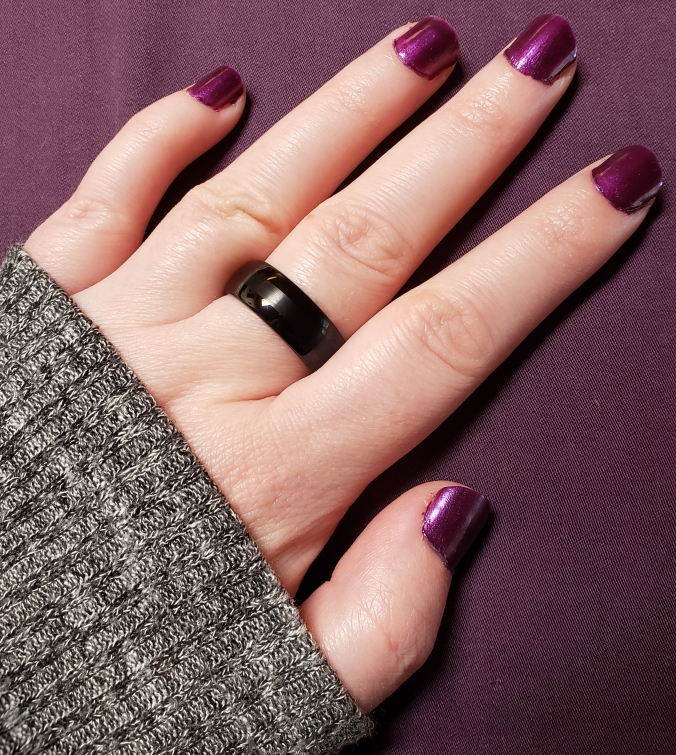 A photo of my black ace ring on my left hand. I am wearing purple nail polish and you cab see the edge of my gray sweater partly covering my hand.